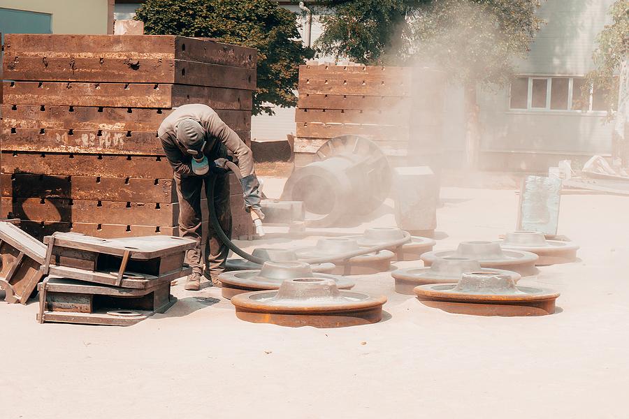 A worker doing a concrete sandblasting