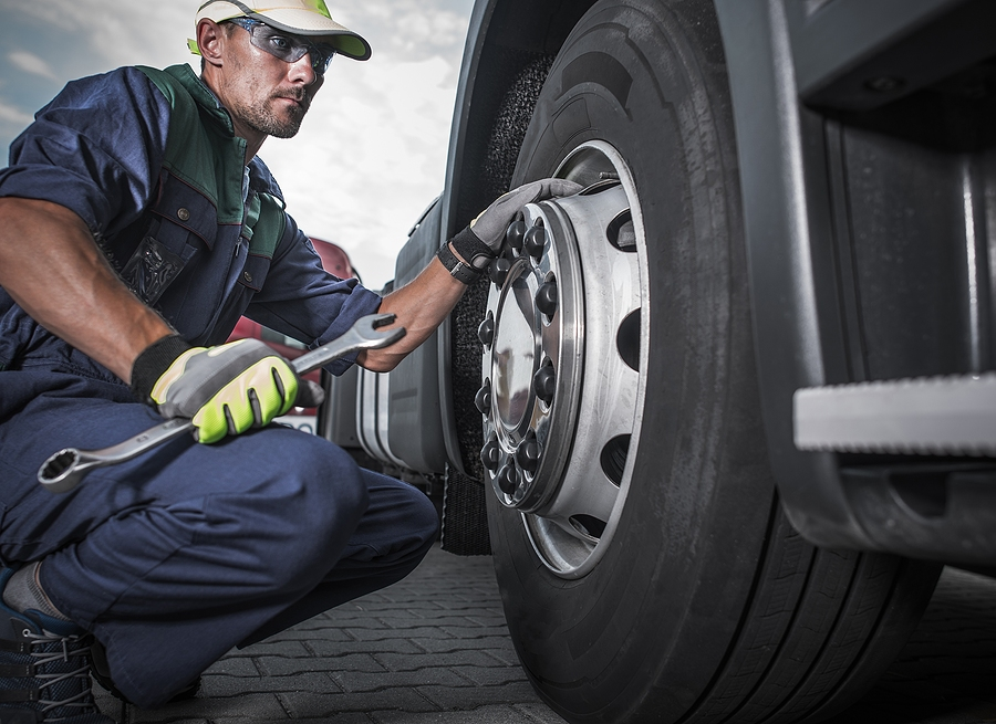 Worker using a mobile truck tyre changer
