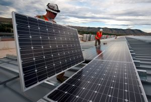 Two workers providing commercial solar financing options and installation