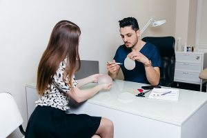 Professional breast surgeon in Berwick shows an implant to a female client